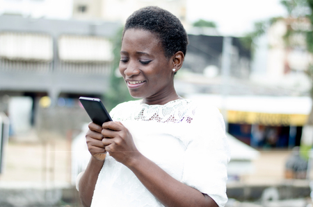 Young woman writes on mobile phones and smiles. Banque d'images