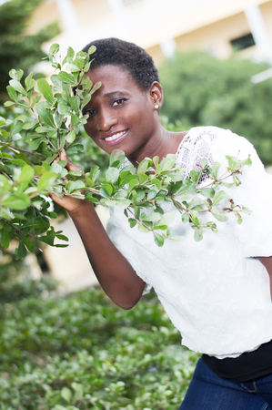Smiling young woman hidden behind foliage looks through.
