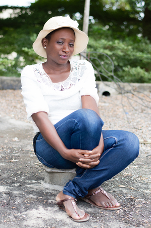 Young woman sitting on a piece of brick in height on a slab.