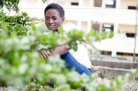 Young smiling woman sitting behind the foliage.
