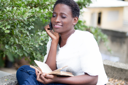 Young woman sitting with a book in hand by calling. Banque d'images