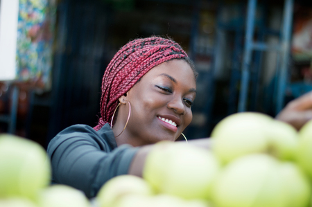 Smiling young woman choosing behind a shelf at an apple at street market