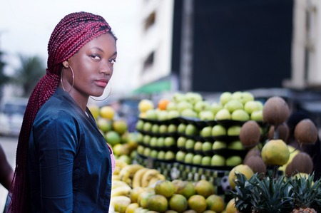 Young woman standing in front of shelves of fruit, looking at the camera.