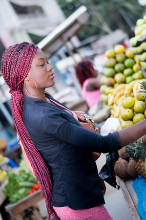 Beautiful young woman buying fruit at the market. Banque d'images