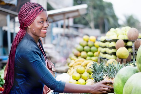 Smiling young woman with a handbag making her choice at fruits market.