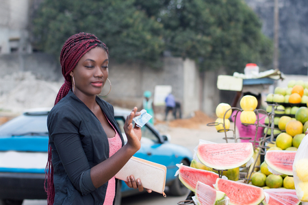 Young woman shows a bank note to the vendor at street fruit market. Banque d'images