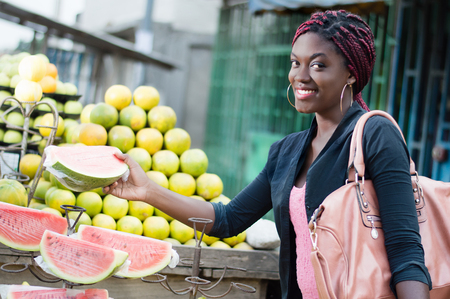 Smiling young woman grabs a slice of ripe fruit in a street market.