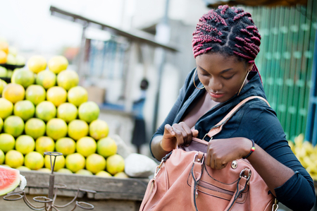 Young woman standing in front of a fruit shelf, rummages in her handbag.