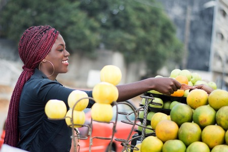 Smiling young woman takes her money in the hand of the fruit seller Banque d'images