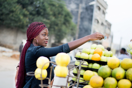 Young woman buys fruit on the street market placed on shelves