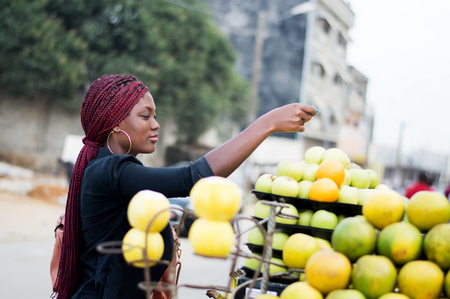 Young woman buys fruit on the street market placed on shelves. Banque d'images