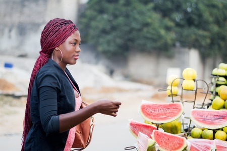 Young woman at street fruit market and ready to pay. Banque d'images