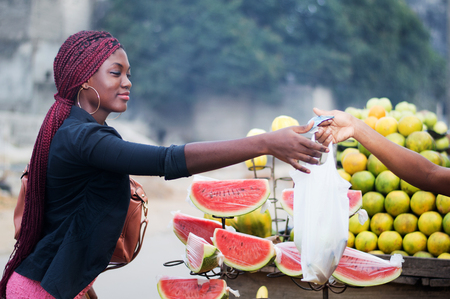 Young woman gives money to the fruit vendor.