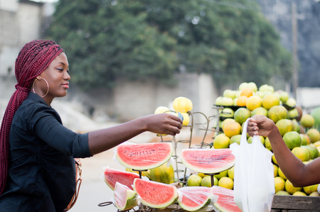 Young woman gives a banknote to the vendor at street fruit market. Banque d'images
