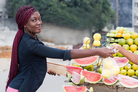 Pretty young woman buys food at street market.