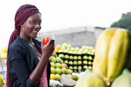 Smiling young woman shows a ripe tomato looking at the camera. Banque d'images