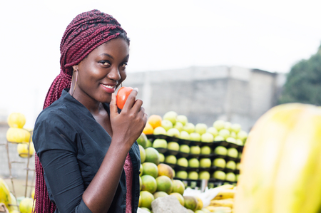 Smiling young woman holding a tomato and tasted.