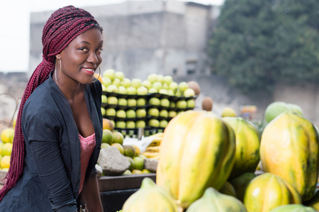 Smiling young woman standing between shelves of fruit and looking at the camera.