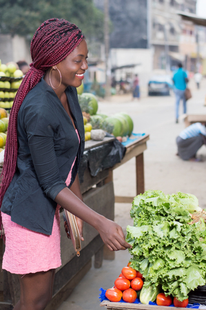 Smiling young woman asks the price of a kilogram of vegetables.