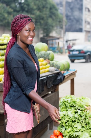 Smiling young woman asks the price of a kilogram of vegetables