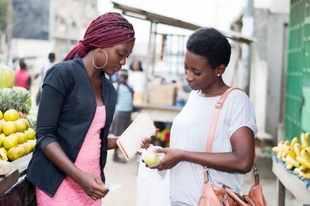 Two young women at fruit market carefully watching an apple.