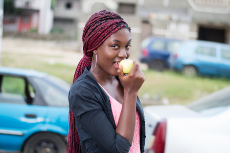 Young woman enjoying an apple and looking at the camera.