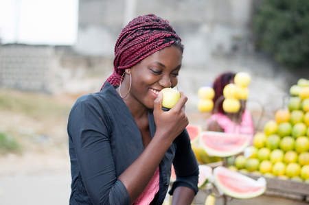 Smiling young woman standing near a fruit shelf is eating an apple. Stock Photo