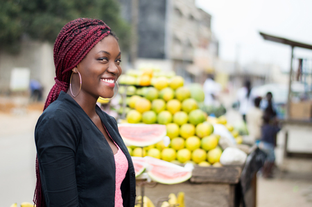 Portrait of smiling young woman standing near a table with a bunch of fruit.