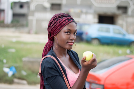 Young and beautiful woman holding an apple is standing at the edge of the road. Banque d'images