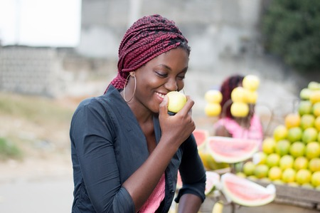 Smiling young woman standing near a fruit shelf is eating an apple. Banque d'images