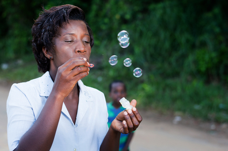 pretty young woman blowing bubbles and her child looks in the background. Banque d'images