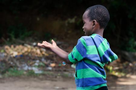 Le petit garçon veut attraper les bulles soufflées par sa mère. Banque d'images - 87492718