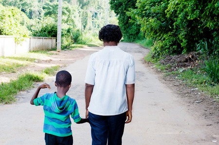Young woman holding the hand of her child and walk on the country road.