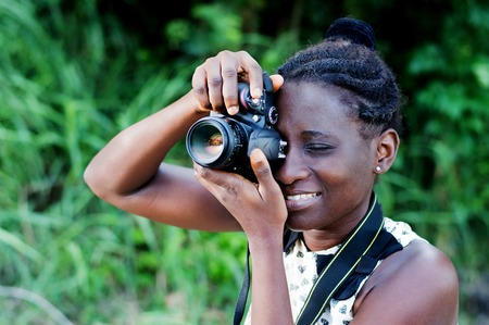 Travel, tourism and hobby. Young woman photographer taking pictures in the bush.