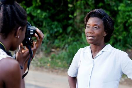 Jeune femme prenant une photo avec sa copine à l'extérieur de la forêt Banque d'images - 87422688