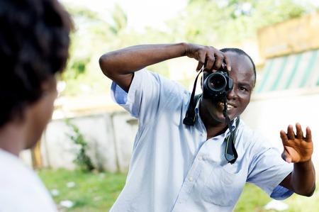 Souriante jeune photographe prenant une pose à son modèle et lui demandant de position Banque d'images - 87549504