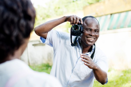 Souriante jeune photographe prenant une pose à son modèle et lui demandant de position Banque d'images - 87422690