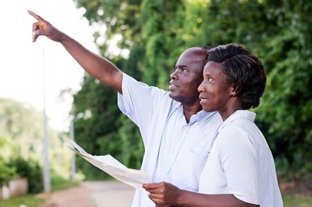 Couple heureux marchant dans la campagne et des points à quelque chose. Banque d'images - 87723750