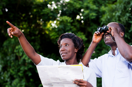 young woman pointing at the young man looking through binoculars.
