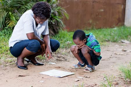 Dans les voyages et le tourisme, une jeune mère lit une carte avec son enfant à la campagne. Banque d'images - 87723992