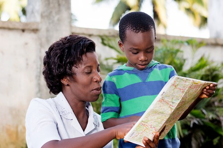 In travel and tourism, a young mother reads a map with her child in the country. Banque d'images