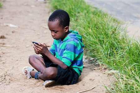 child sitting on the floor making games in a mobile phone in hand. Banque d'images - 95666530