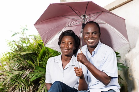 happy adult couple sitting and protecting themselves with an umbrella near a flower. Banque d'images