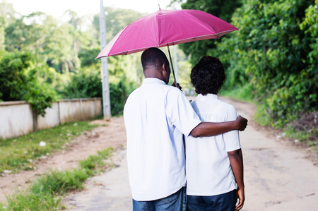 young couples stroll and covered by an umbrella. Banque d'images