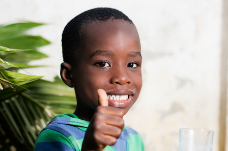 Happy child in a sign of appreciation after drinking a glass of milk. Banque d'images - 96838338