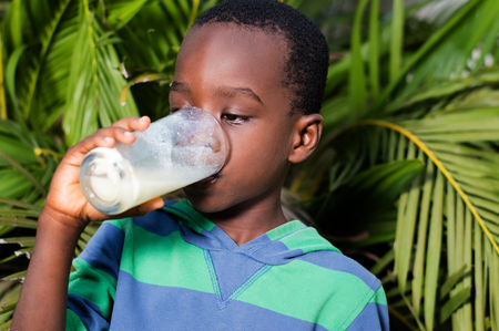 boy drinks milk behind the house near a flower. Banque d'images - 96858566