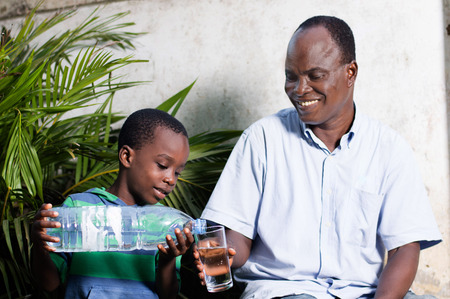 child out of the water in a glass to his smiling father. Banque d'images - 96838344