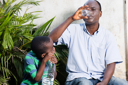 middle-aged man drinks water in a glass and child watching. Banque d'images - 96838341