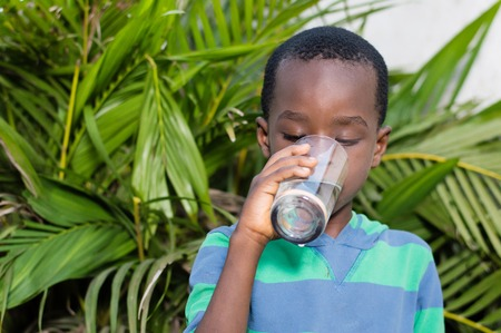 Boy drinking mineral water in a glass. Banque d'images - 96785680