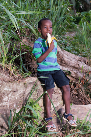 Boy sitting on a tree eating a banana with pleasure. Banque d'images - 96793977